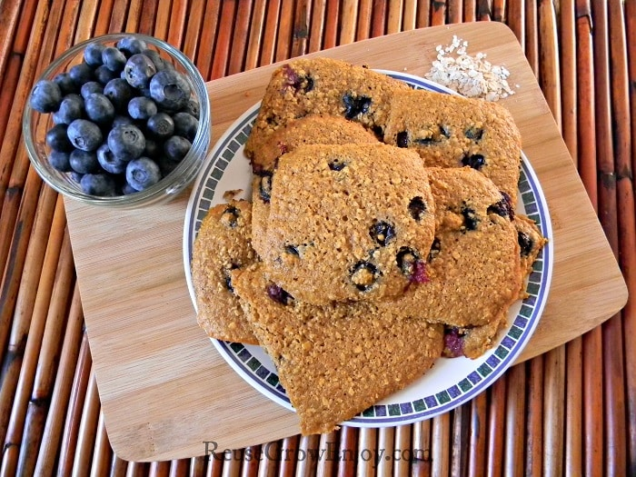 Blueberry oatmeal cookies on white plate with blue trim sitting on a wood cutting board with bowl of fresh blueberries to left side