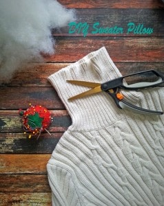 White sweater laying on wood background with cotton stuffing pin cushion. Text overlay at top that says DIY Sweater Pillow