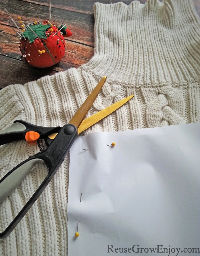 Paper pattern pinned to sweater with scissors laying on the side