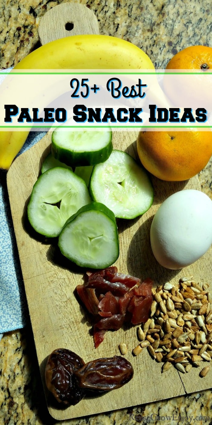 "A wood cutting board with egg, jerky, sunflower seeds, dates, banana, cucumber slices and oranges with a text overlay that says - ""25+ Best Paleo Snack Ideas"""