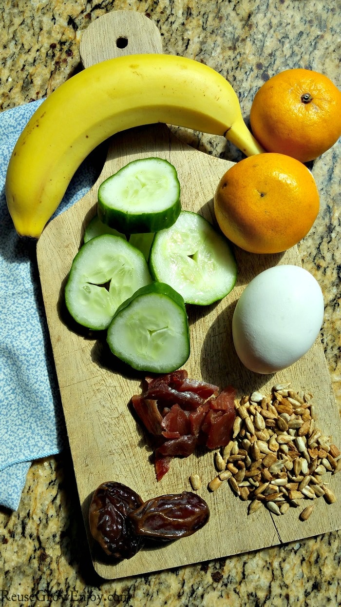 A wood cutting board with egg, jerky, sunflower seeds, dates, banana, cucumber slices and oranges for Paleo snack ideas