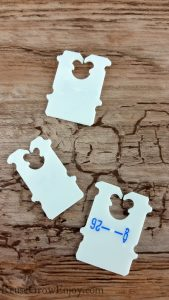 3 white Bread clips laying on wood looking background