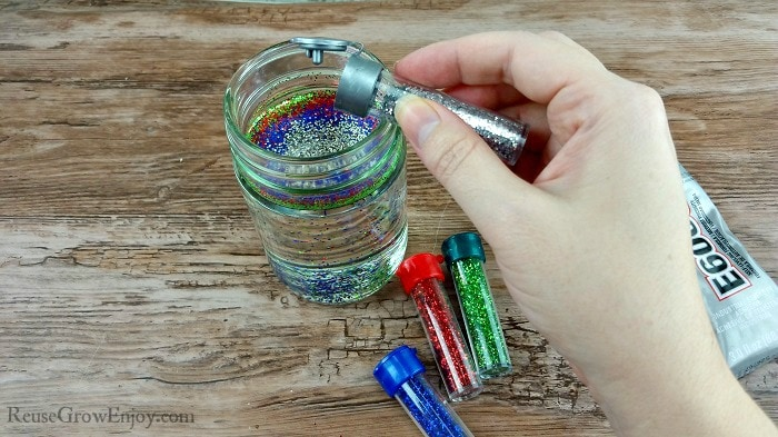 Hand adding different colors glitters to jar filled with oil.