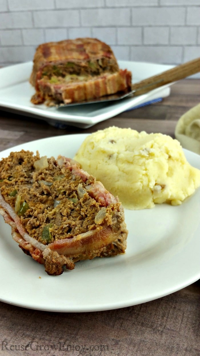 A slice of bacon wrapped Whole30 meatloaf on a small white plate with a serving of mashed potatoes beside it. In the background is the rest of the meatloaf on a white plate.