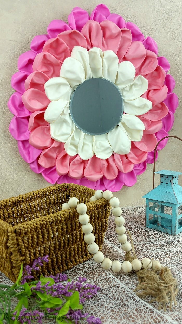 Balloon craft wall art hanging on wall with mirror in center. Small basket with beads in front and a candle holder on right.