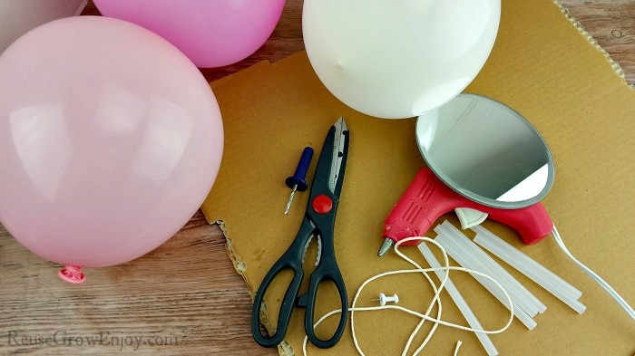 Balloon craft supplies, pink and white balloons, thumbtack, scissors, hot glue gun, cardboard, string and mirror.
