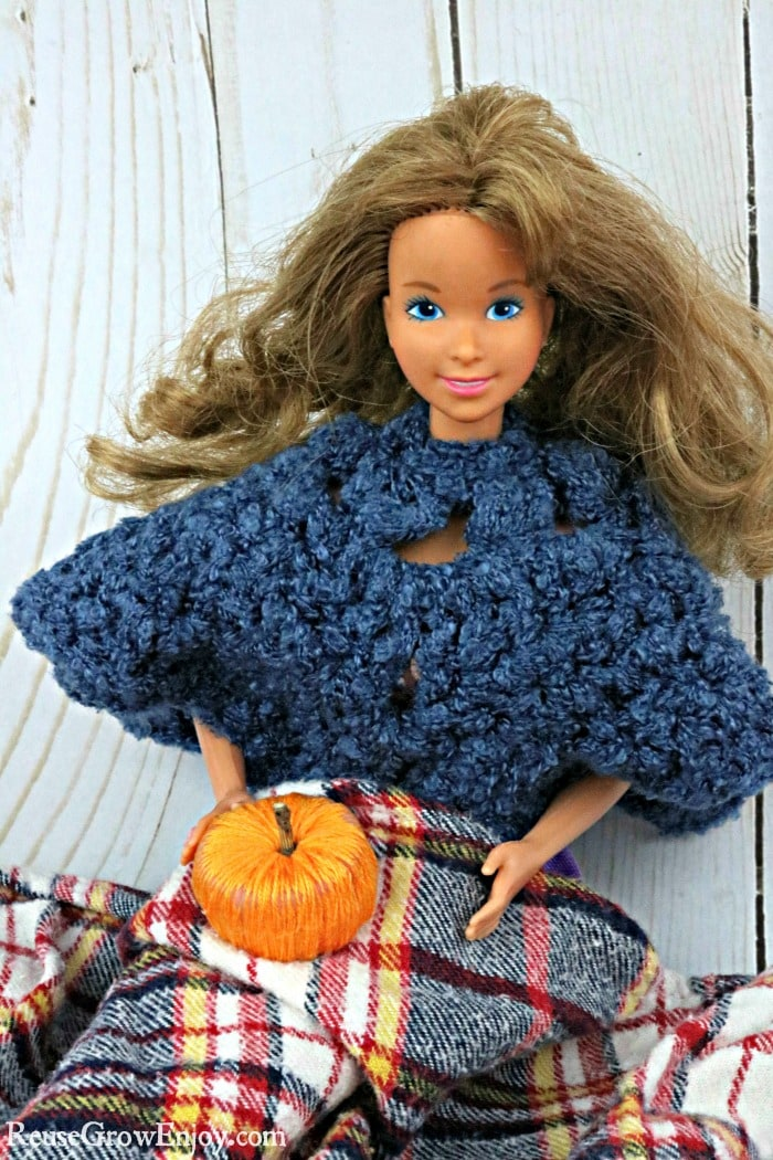Barbie holding pumpkin on lap with blanket
