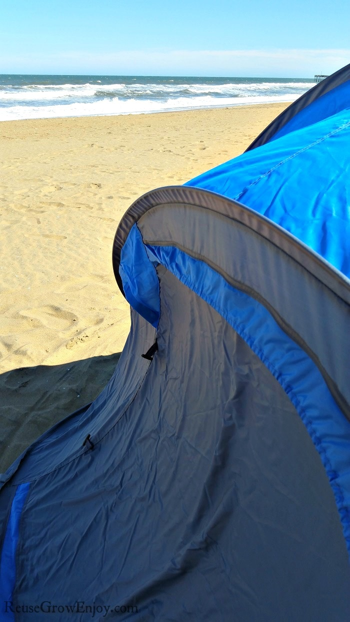 Tent on the beach with ocean in background.