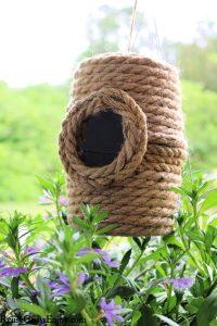 Beehive DIY birdhouse hanging over purple flowers