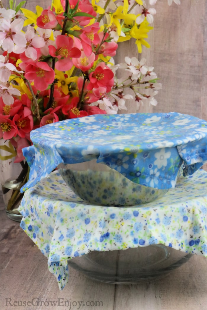 Two bowls stacked each with a beeswax wrap over them fresh spring flowers in background