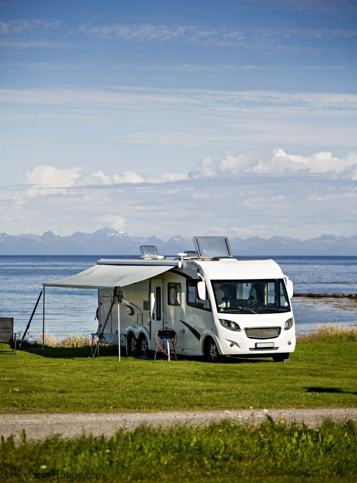 RV camping by water with green grass around it.