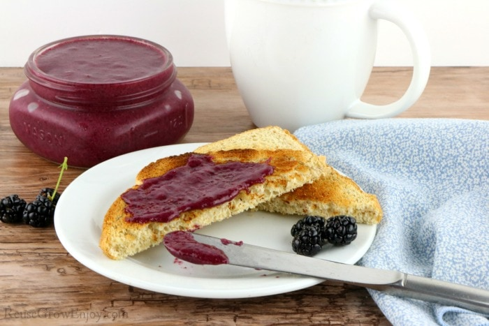 Toast on white plate covered in blackberry jelly with jar of jelly in background with coffee mug