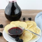 Bottle of blackberry syrup in background. Front is a white plate with bite size pancakes and a dish of the syrup