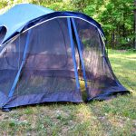 Dark blue tent set up on grass camping for free.