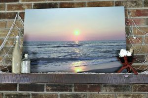Sunrise over ocean canvas print on shelf with beach items around.