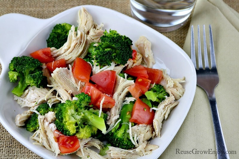White plate with tomatoes, broccoli and lemon pepper chicken fork at right side of plate.