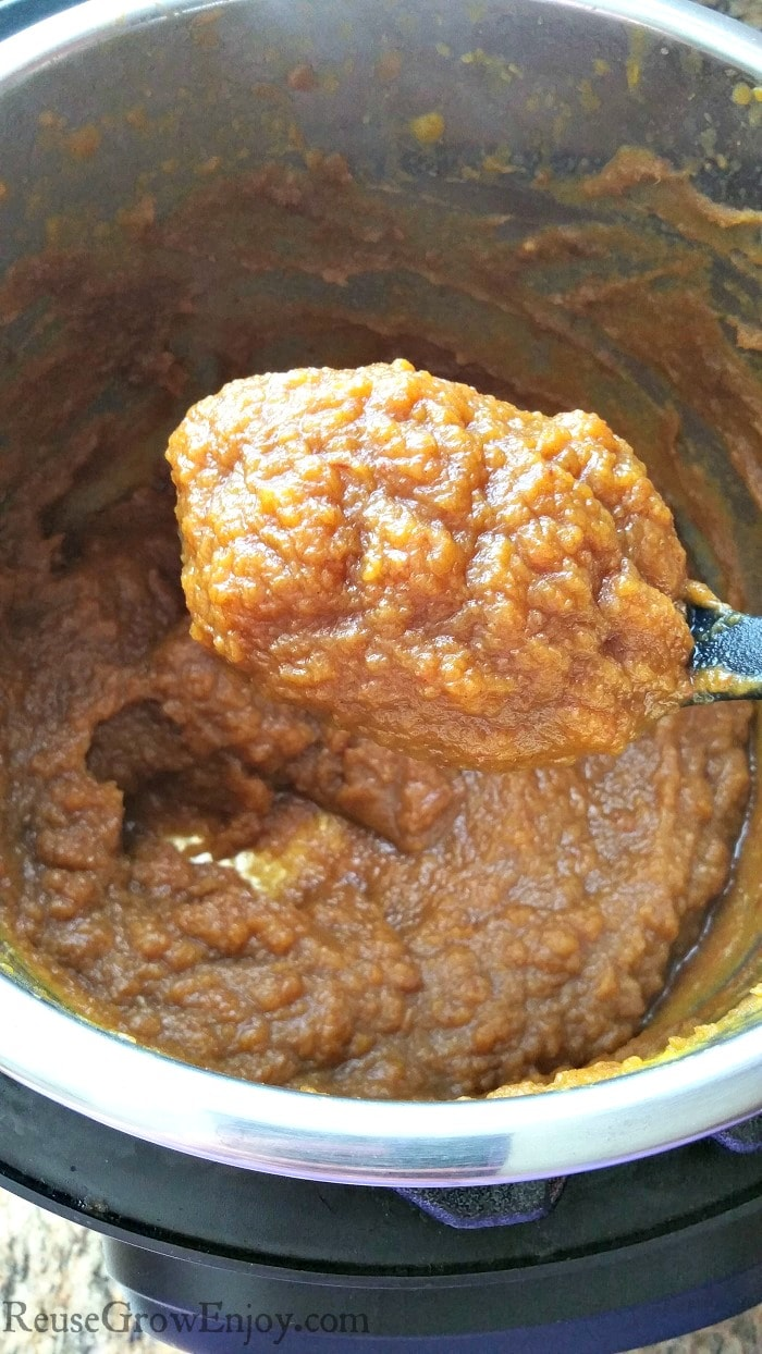 Instant Pot pumpkin butter cooked down to a thickness so that it sticks to a black mixing spoon.