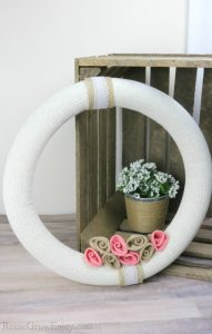 Finished wreath with wood crate and white flower in background