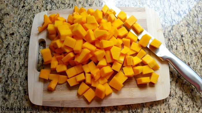 Cubed butternut squash on cutting board with knife