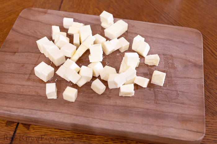 Butter cut into cubes on wood cutting board.