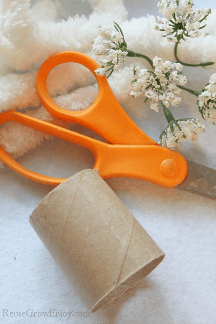 Cut cardboard tube. Yarn and scissors in background.