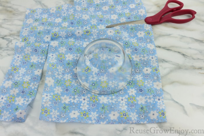 Scissors cutting fabric with glass bowl on fabric