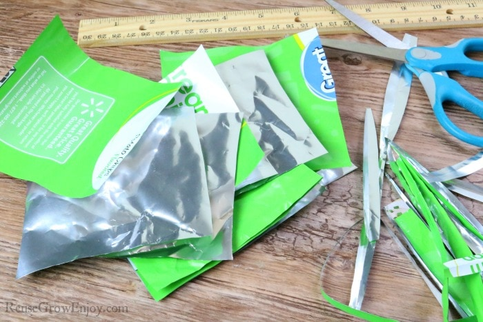Stack of square pieces of cut chip bags with scrap ends, scissors and wood ruler off to side.