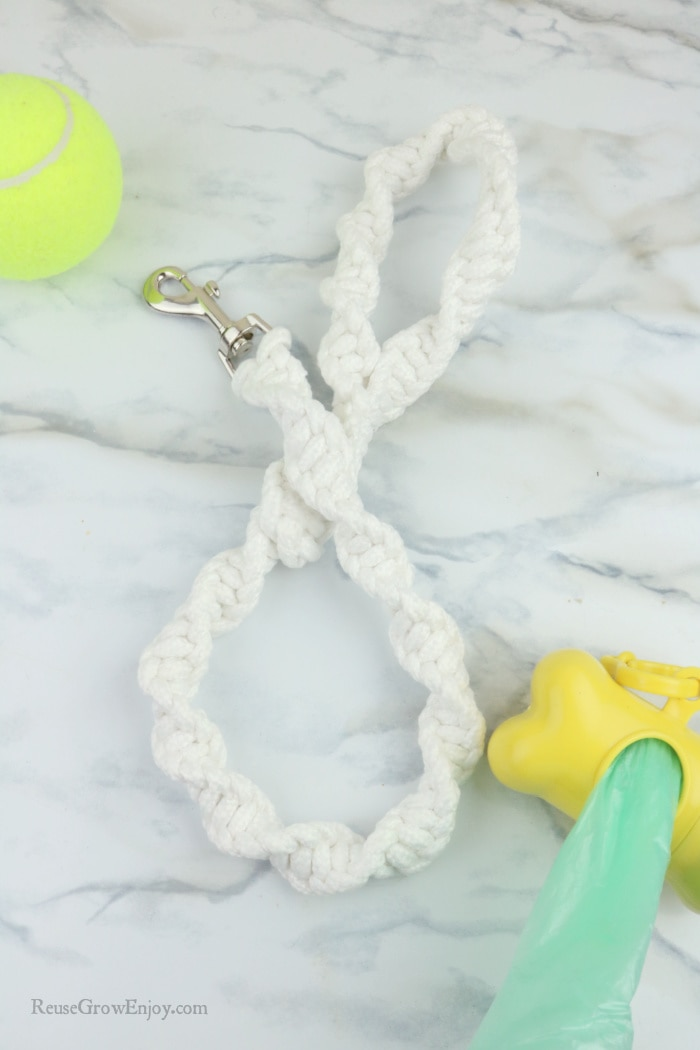 Finished white leash with ball and doggy bag holder to the side