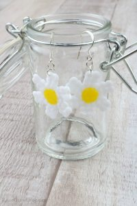 Finished daisy earrings hanging on side of glass jar