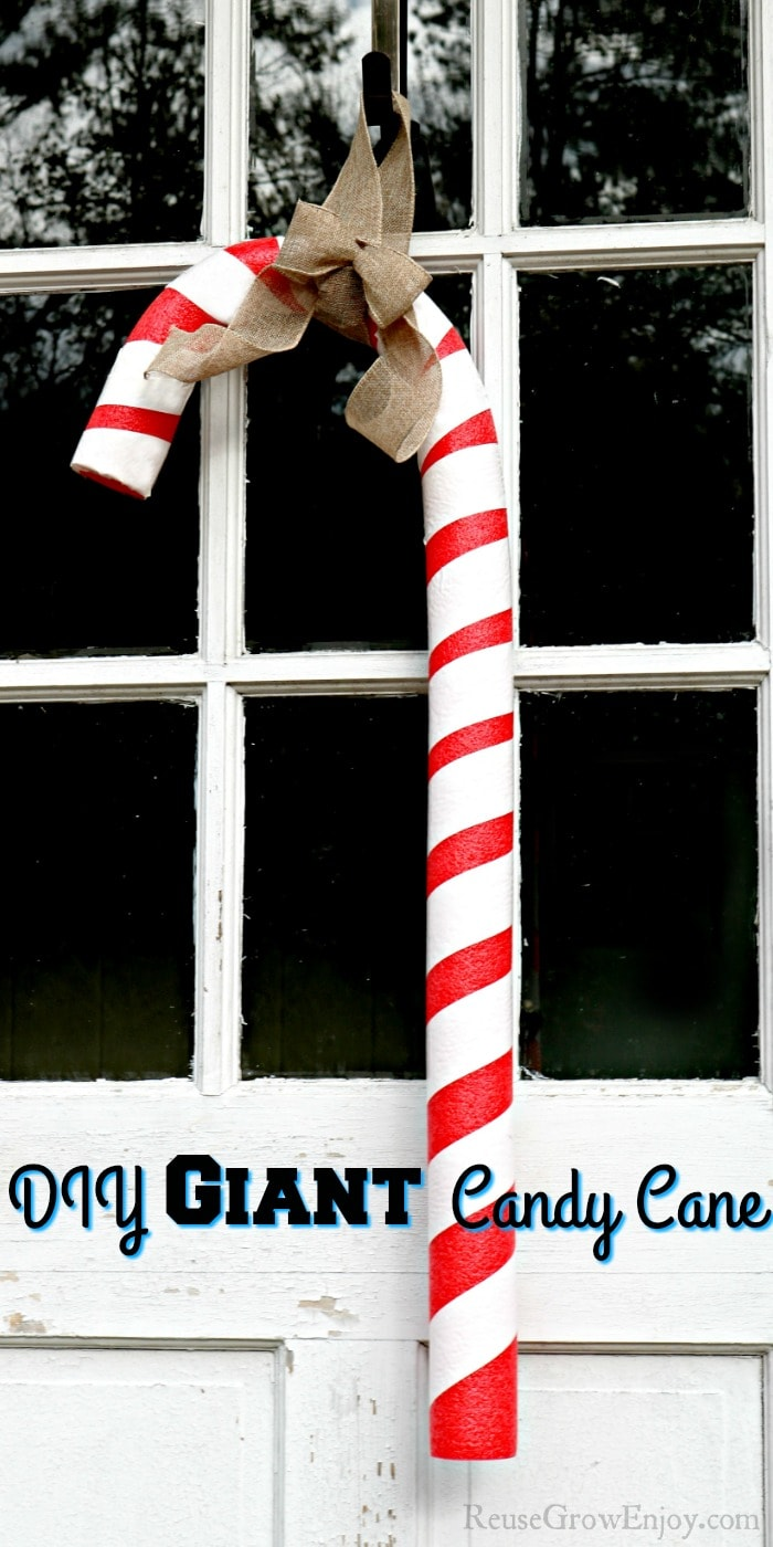 Giant candy cane hanging on a door with windows with text overlay at the bottom.