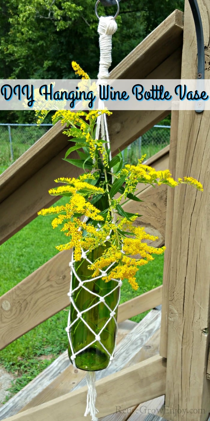 """Bottle vase hanging outside with yellow flowers. Text overlay that says """"DIY Hanging Wine Bottle Vase"""""""
