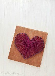 Heart string art on wood board with purple string.