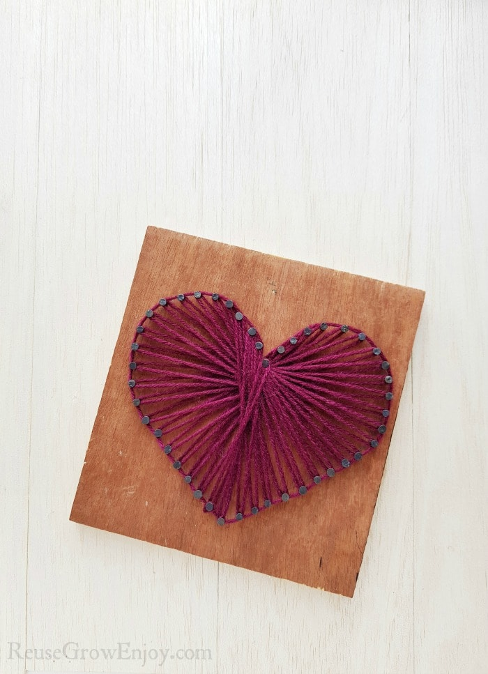 Heart string art on wood board with purple string.