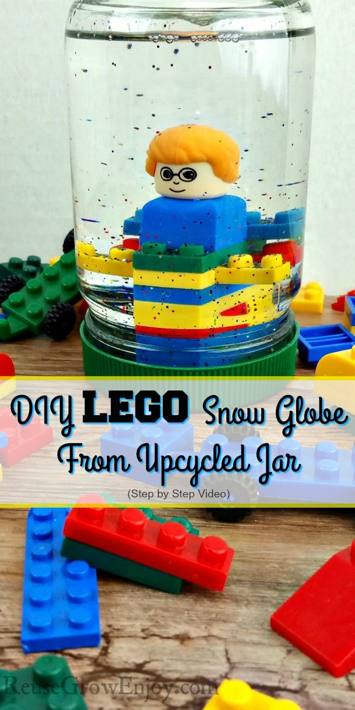 "Small LEGOs all around with a upcycled mayo jar turned LEGO snow globe in the center that has LEGOs inside with glitter. Text overlay that says ""DIY Lego Snow Globe From Upcycled Jar""."