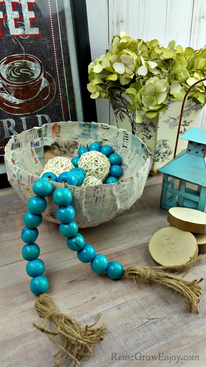 DIY paper mache bowl with farmstyle beads in it and picture and flowers in the background.
