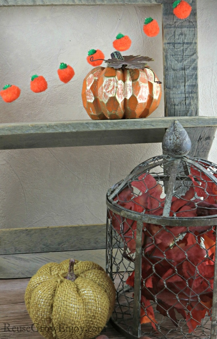 Pumpkin garland hanging on barn wood shelf with fall decor in the front.