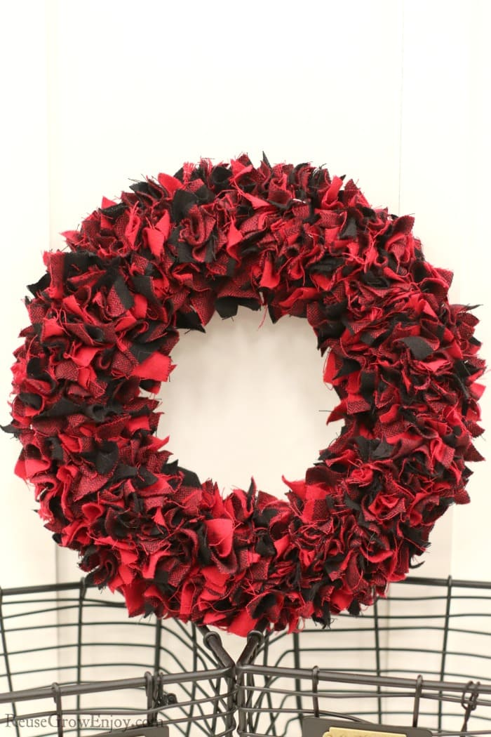 Red and black fabric wreath laying on wire baskets
