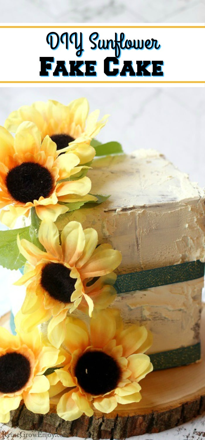 "A finished fake cake prop with sunflowers and green ribbon. It is on a wood slice. Text overlay that says ""DIY Sunflower Fake Cake""."