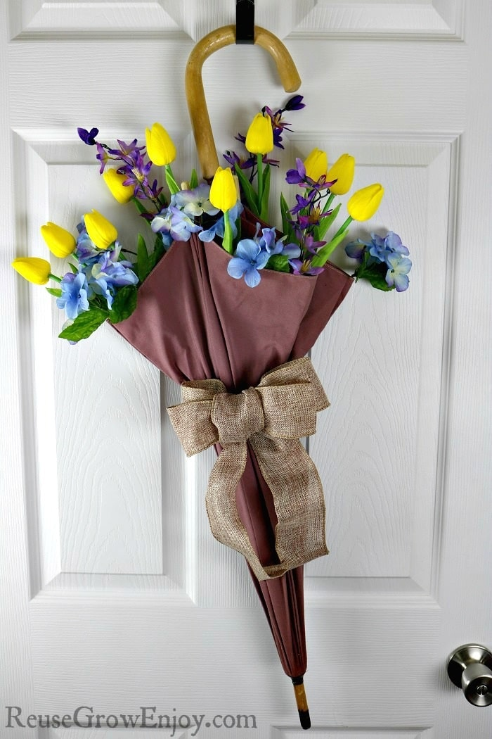 If you have an old umbrella, don't toss it out. They make for a super easy and cute DIY Upcycled Umbrella Flower Arrangement!