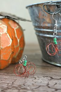 Pair of wire pumpkin earrings with a fake pumpkin and tin in the background.