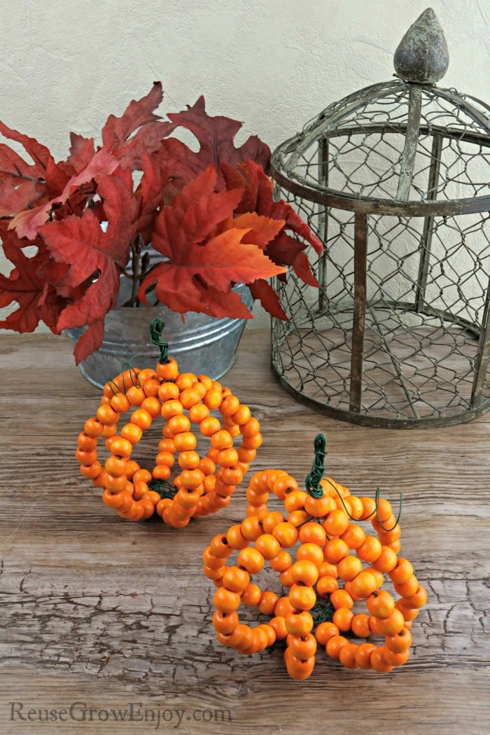 Wood bead pumpkins with read leaves and wire decor in background.