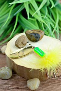Dad Fishing Gift Idea- Hand stamped fishing lure laying on wood with rocks.