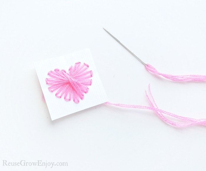 Needle with pink thread on white paper background, small cardstock paper with a heart shape made from holes punched in paper. Pink thread pulled through the holes on the paper and a dotted stick on the edge of the heart.