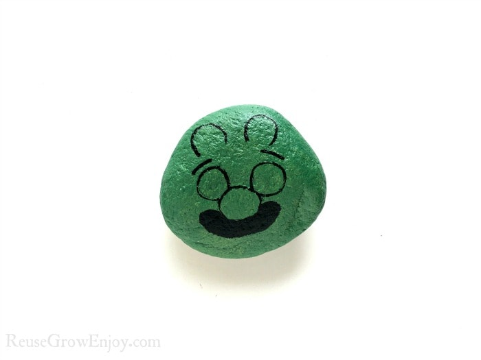 Draw face on green rock