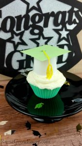 Graduation cupcake toppers on a cupcake on a black cake stand.