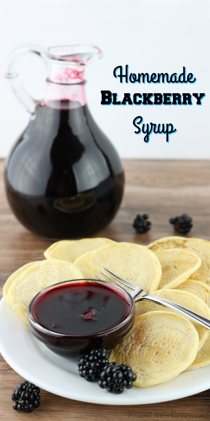 "Bottle of blackberry syrup in background. Front is a white plate with bite size pancakes and a dish of the syrup. Text overlay at top that says ""Homemade Blackberry Syrup"""