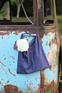 Blue with dots upcycled pillowcase bag hanging on door knob of old rusty truck.