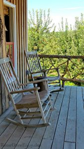 Old style porch with two wood rocking chairs, apple trees in the background.