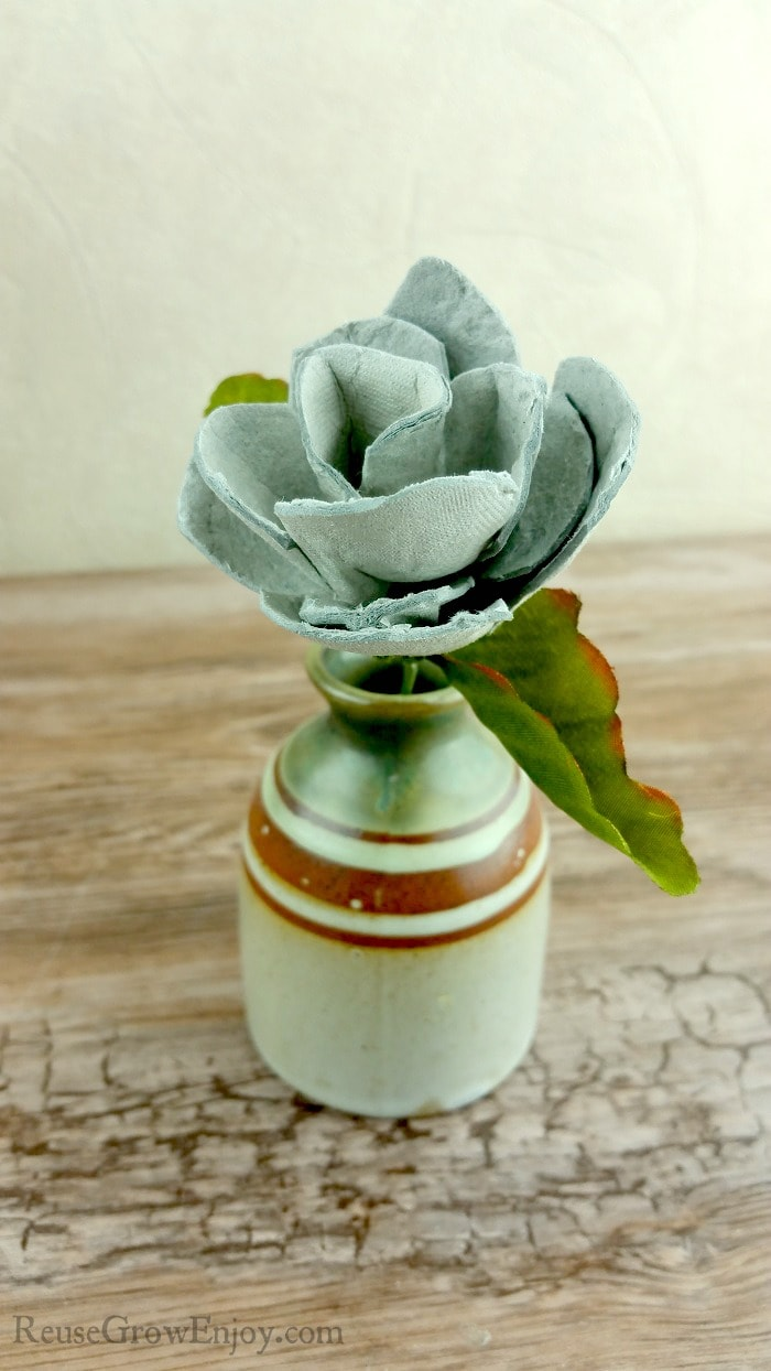 A rose made from egg cartons standing in a jug vase.
