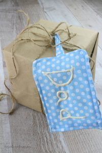 Small box wrapped in brown paper with twine bow and blue and white dotted fabric gift tag hanging off